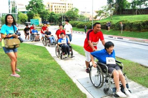 Volunteer and wheelchair users participating in the Bizad Charity Run 2013