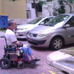 Wheelchair user obstructed from using ramp to building by a car parked in front of the ramp.
